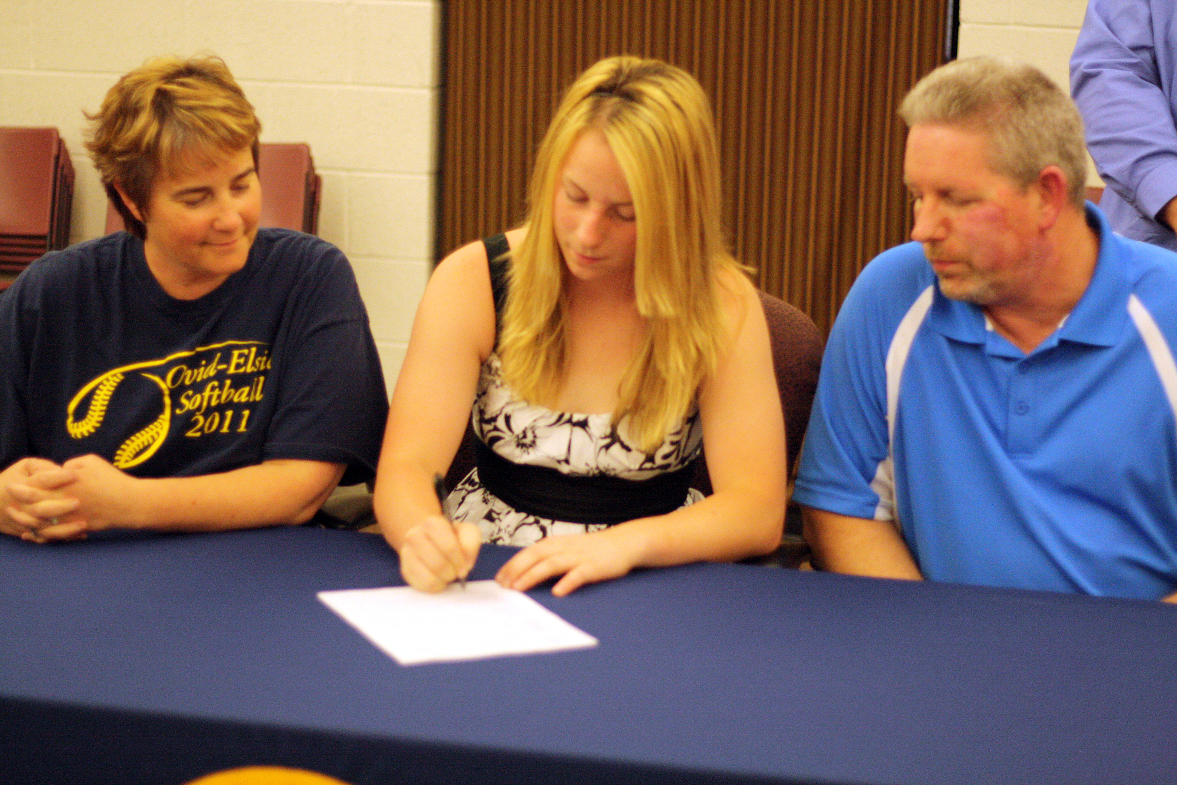 With her parents looking on, senior Alyson Rose signs a letter of intent to play softball at Brown Mackie College in Kansas.