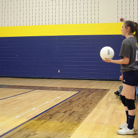 8th grader Vivian Cole winding up to serve against St. Louis. \Photo b Alexis Underwood