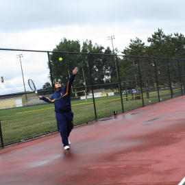 Junior Kyle Wendling tosses up for a serve during practice for upcoming games. | Photo by Miranda Chapman