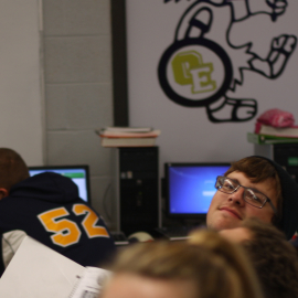Junior Kyle Wendling pokes his head out as he works in computer lab. |Photo by: Jeanelle Courtnay