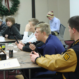 Juniors Conner Applebee (middle) and Clayton Alaga (right) wait impatiently for the next toss-up question at the last Quiz Bowl match on December 11, at the Gratiot- Isabella RESD. | Photo by Molly Maynard